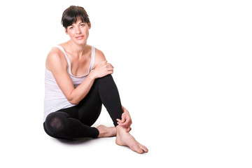 Athletic young woman relaxes, sitting, on white