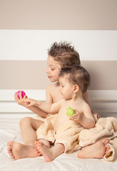 Boy and baby with wet hair under towels playing