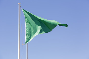 Green flag against blue sky background