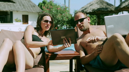 Couple comparing results together in swimming pool, steadycam sh