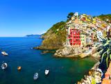 Riomaggiore village, rocks, boats and sea at sunset. Cinque Terr