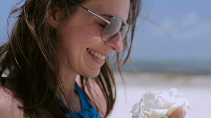 Woman smelling beautiful flower on the beach, closeup, steadycam