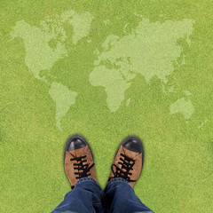 Pair of shoes standing on green background with world map