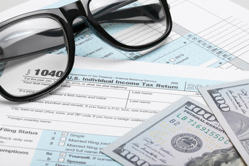 USA Tax Form 1040 with dollars and glasses
