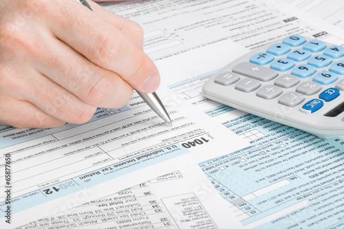 USA Tax Form 1040 - man filling out tax form