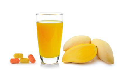 mango juice in a glass and vitamin C over white background