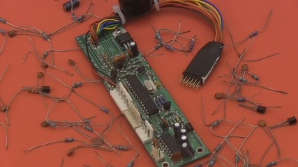 Electronic circuit rotating on a red background.
