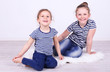 Beautiful small girls sitting on floor on wall background