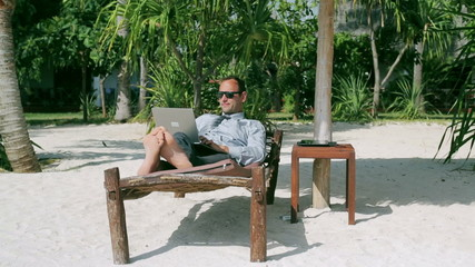 Businessman working on laptop and lying on sunbed