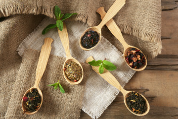 Assortment of dry tea in wooden spoons on table