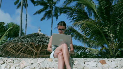Businesswoman working on laptop in exotic place