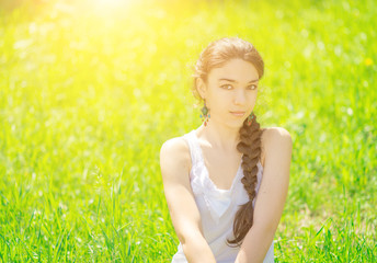 Beautiful girl sitting on grass. With sunshine.