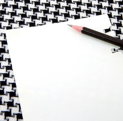 White note pad and pencil on houndstooth pattern cotton.