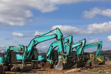 Green earthmoving machines ready for action on housing project