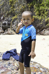 Young kid with swimsuit give thumbs up on tropical beach