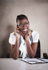 Young attractive african business woman sitting at office desk