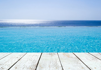 Infinity swimming pool  and empty wooden plank