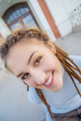 Girl with dreadlocks laughs