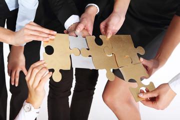 Stalowe puzzle.Grupa ludzi prezentuje srebrno złote puzzle