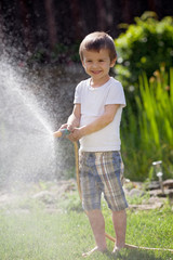 Boy, splashing water with a hose, having fun