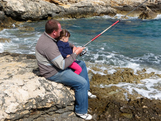 father and daughter fishing on sea on summer day