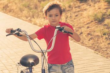 Urban biking - small boy and bike in city park