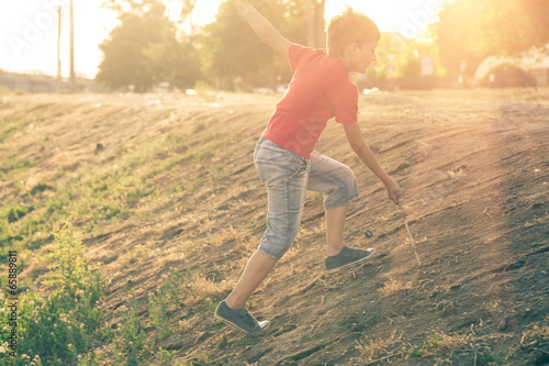 Summertime happyness image of boy climb up slope backlit