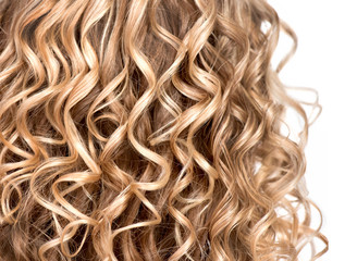 Wavy curly blonde hair closeup. Texture of permed hair