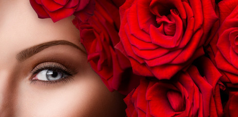 Close-up of beautiful woman blue eye with red roses
