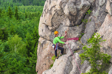 Man climbs a vertical wall of one of the rocks against forest