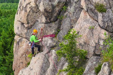 Man climbs a vertical wall of one of the rocks against green