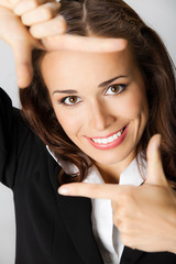 Businesswoman framing her face with hands, over grey