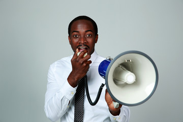 African man shouting through a megaphone on gray background