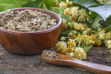 linden tea in a wooden bowl and scoop surrounded by flowers