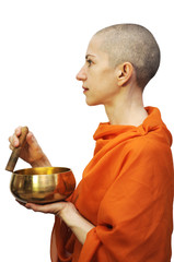 Bald woman in saffron robe with singing bowl, meditating
