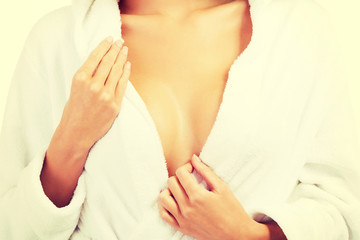 Woman in bathrobe, close up on chest.