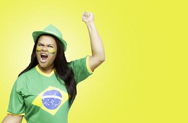 Brazilian fan celebrates on yellow background