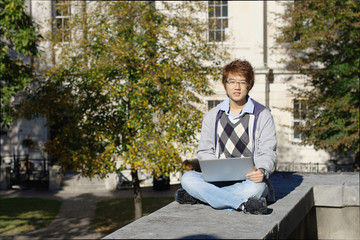 Asian student outdoors with laptop