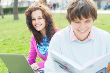 Smiling girl with a laptop with a student at the foreground