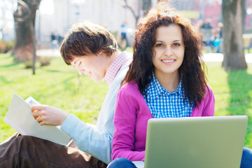 Smiling girl with a laptop with a student at the background