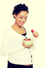 Beautifyl young woman eating strawberries