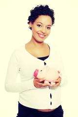Pregnant woman holding piggy bank