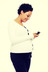 Beautiful pregnant woman dialing a number