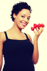 Young happy pregnant woman with strawberries
