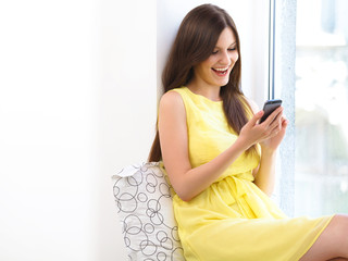 Happy Woman Reading sms on her Mobile Phone.