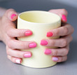 hand with perfect colored manicure and yellow cup of tee