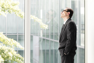 Daydreaming Businessman looking through the window