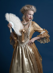 Retro baroque fashion woman wearing gold dress. Holding a fan. S