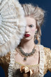 Retro baroque fashion woman wearing gold dress. Holding a fan. S