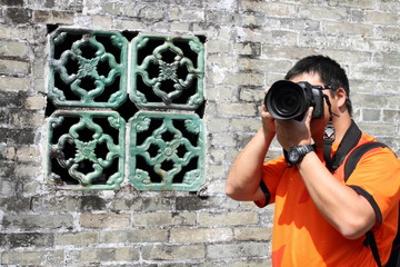 Asian travel photographer touring a traditional village